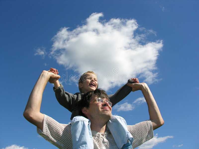 Father with son on shoulders sunny day. Cloud blue sky royalty free stock photography