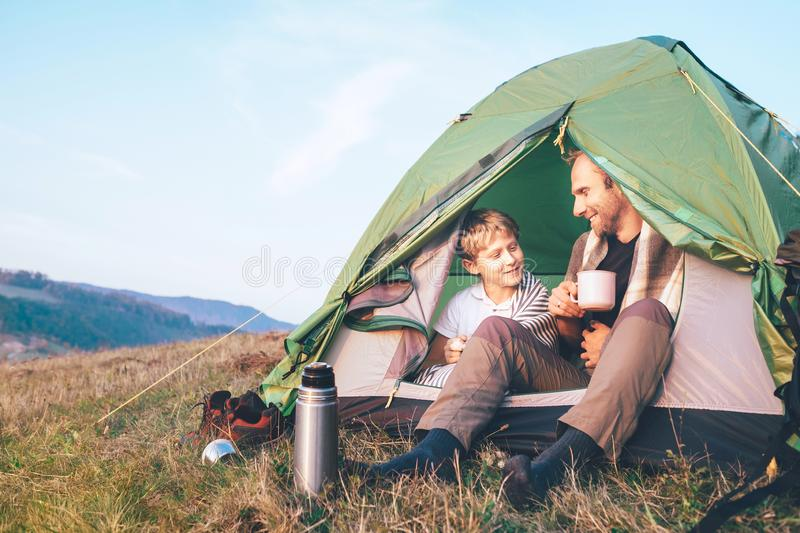 Father and son sit in camp tent drink hot tea and have conversation. Leisure time with father, parenthood stock images