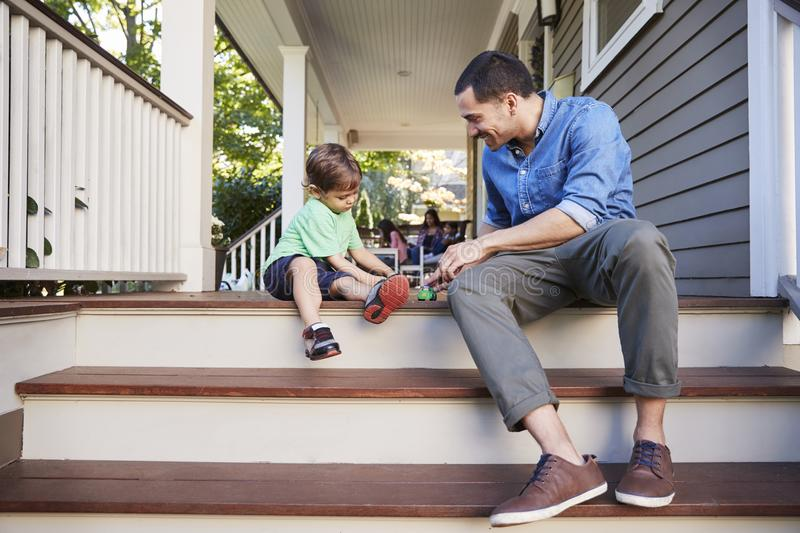 Father And Son Sit On Porch Of House Playing With Toys Together stock image