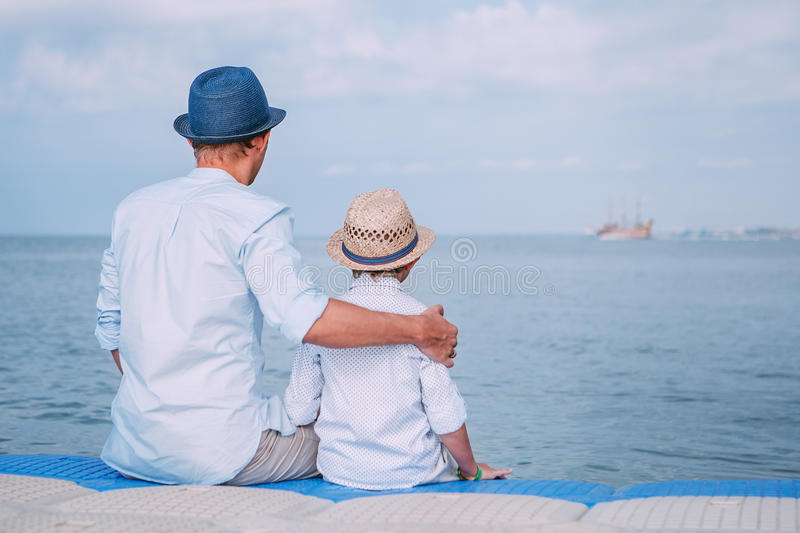 Father and son sit on the sea pier and look on the ship on horizont line stock photo