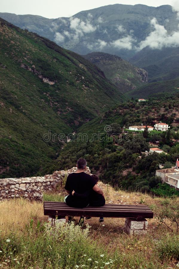 Father and son sitting against mountains. Fathers day concept stock photo
