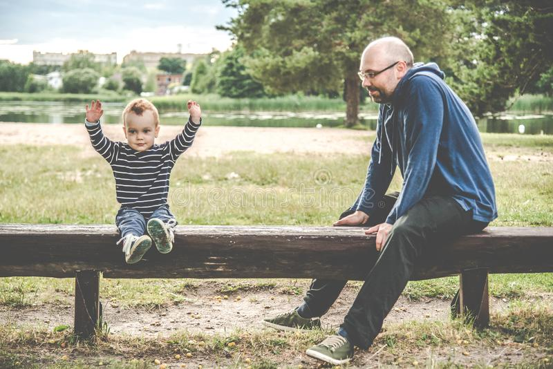 Father and son sitting on a bench stock photo