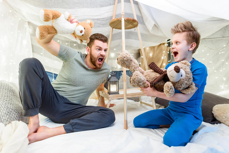 Father and son sitting in blanket fort and playing with teddy bears. Excited father and son sitting in blanket fort and playing with teddy bears royalty free stock photography
