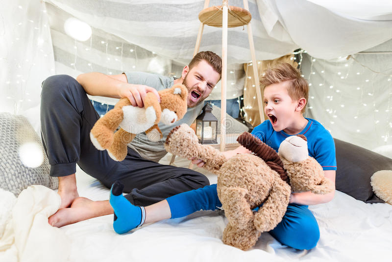Father and son sitting in blanket fort and playing with teddy bears. Excited father and son sitting in blanket fort and playing with teddy bears royalty free stock photos
