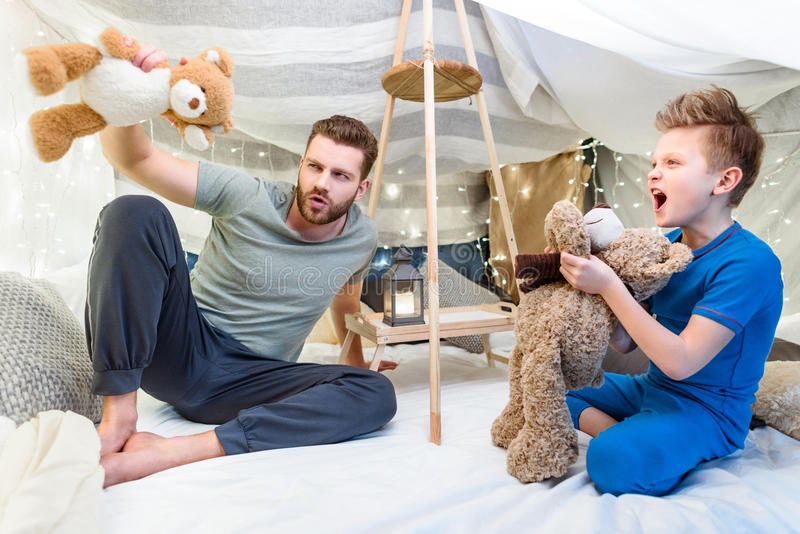Father and son sitting in blanket fort and playing with teddy bears. Happy father and son sitting in blanket fort and playing with teddy bears royalty free stock image