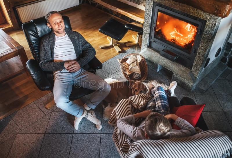 Father with son sitting in comfortable armchairs in their cozy country house near fireplace and enjoying a warm atmosphere and stock photos