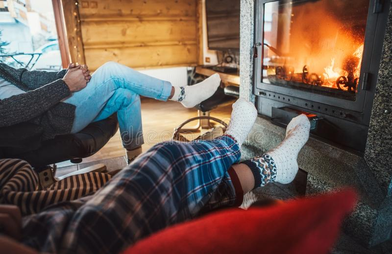Father with son sitting in comfortable armchairs in their cozy country house near fireplace and enjoying a warm atmosphere and royalty free stock image
