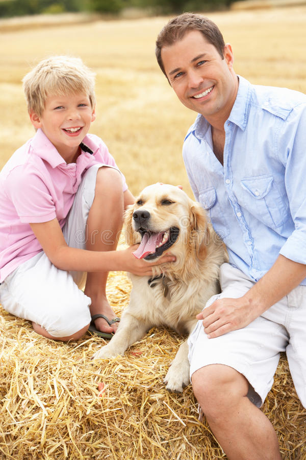 Download Father And Son Sitting With Dog On Straw Bales In Royalty Free Stock Photos - Image: 15548888
