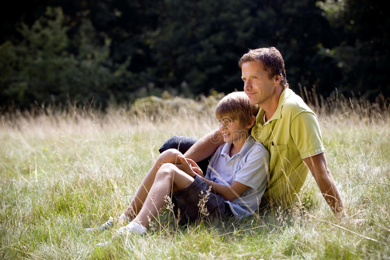 A father and son sitting on the grass stock photo