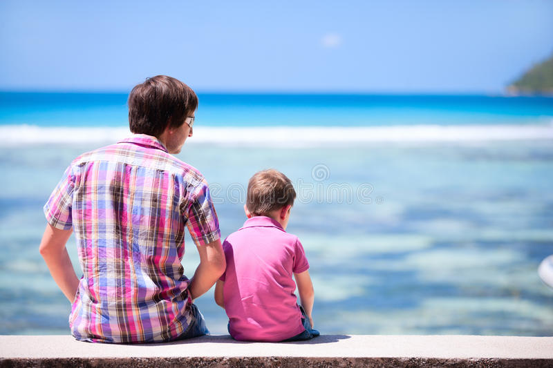 Father and son sitting by the ocean stock photography