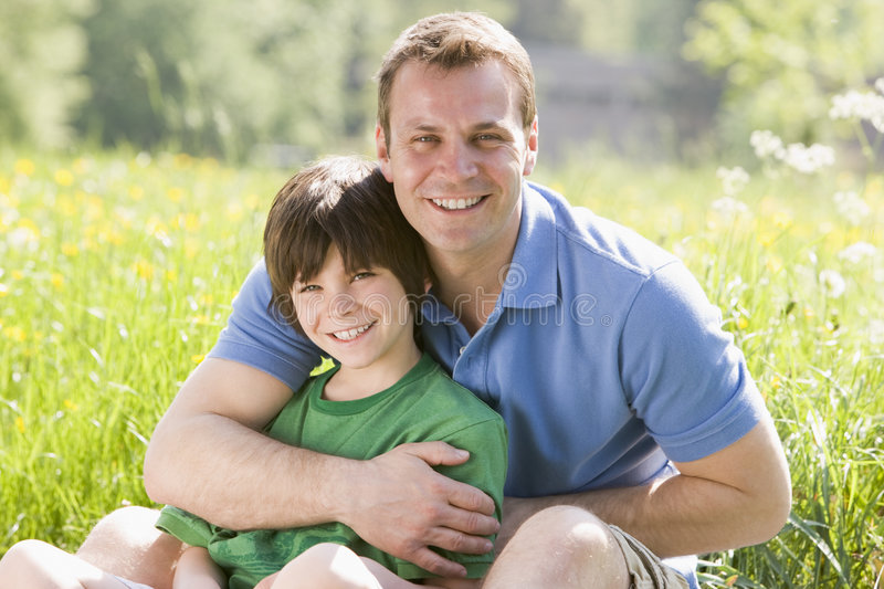 Father and son sitting outdoors smiling stock photos