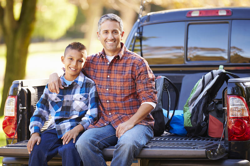 Father And Son Sitting In Pick Up Truck On Camping Holiday. With Arm Around Shoulder Smiling royalty free stock photo