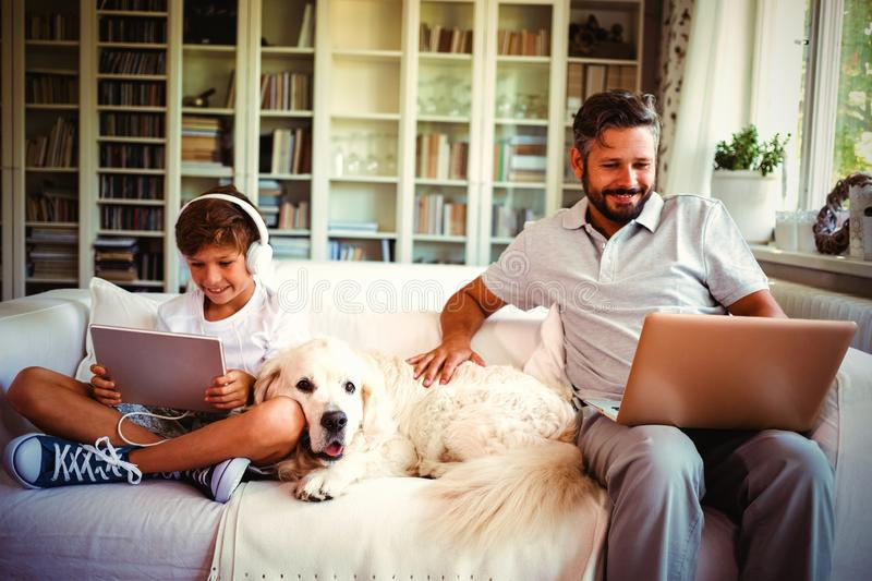 Father and son sitting on sofa and using digital tablet and laptop stock photos