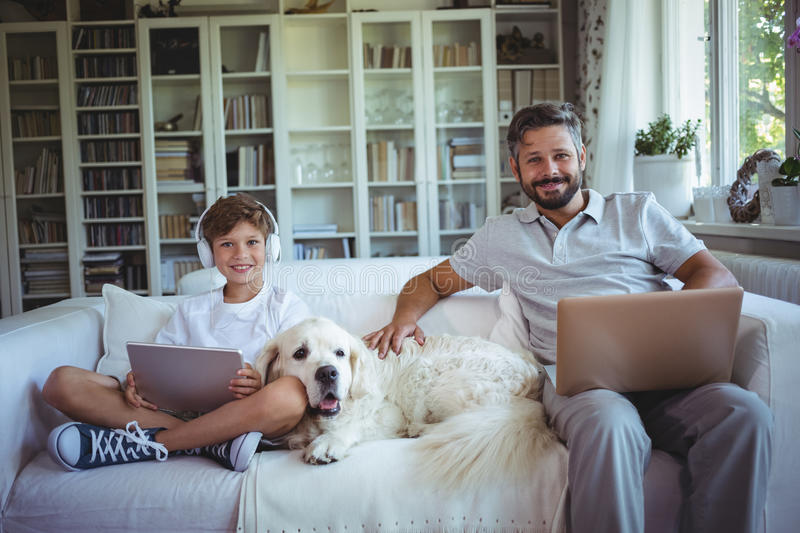Father and son sitting on sofa and using digital tablet and laptop stock images
