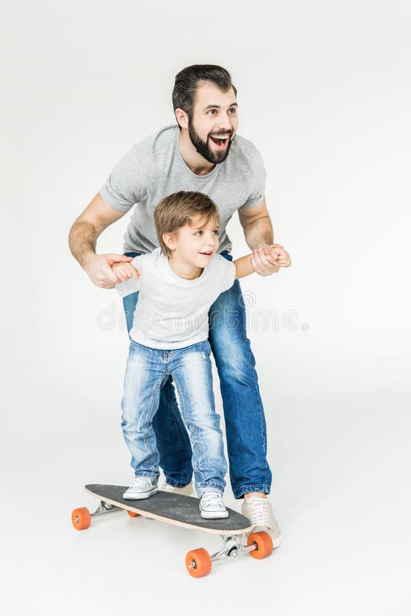 Father and son with skateboard. Happy father teaching cute little son riding skateboard isolated on white stock photography