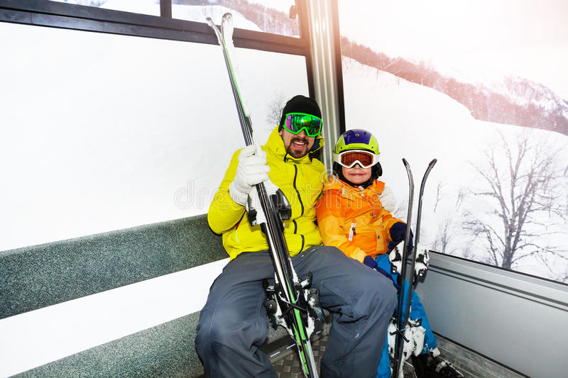 Father and son in ski lift cabin. Dad and son sit in cable car and holding ski lifting up stock photo