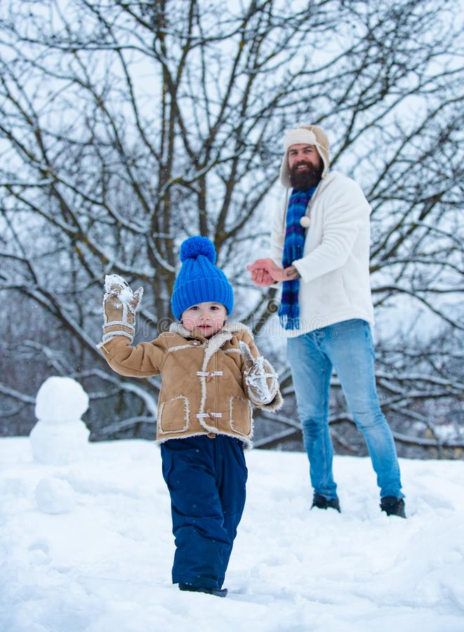 Father and son in snow. Happy father and son - winter portrait. Dad and baby son playing together outdoors. stock image