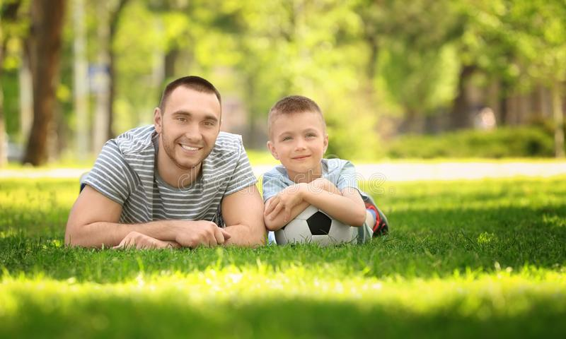 Father and son with soccer ball lying on green grass. In park stock photo