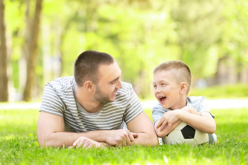 Father and son with soccer ball lying on green grass. In park stock photos