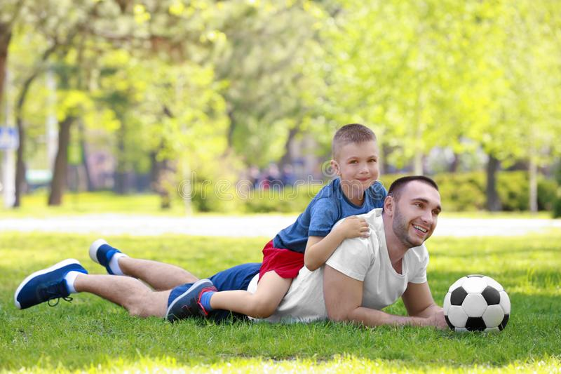 Father and son with soccer ball lying on green grass. In park royalty free stock images