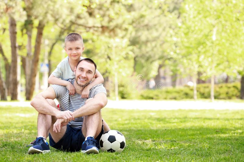 Father and son with soccer ball sitting on green grass. In park royalty free stock photos