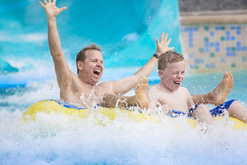 Father and son splashing down a water slide at an aquapark. Thrilling expression of a father and his son as they splash down a water slide at an amusement park royalty free stock image