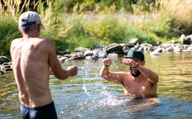 Father and son splashing each other with water in the river stock images
