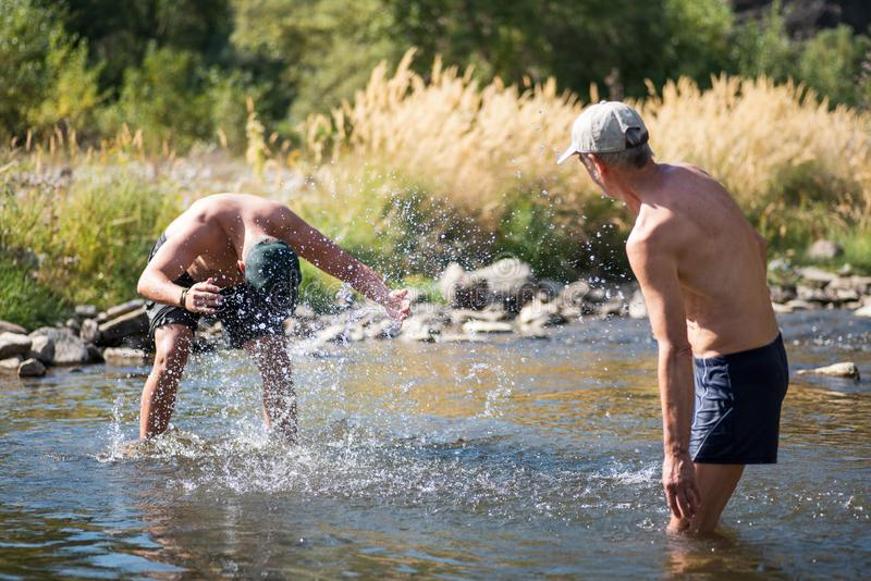 Father and son splashing each other with water in the river royalty free stock photography