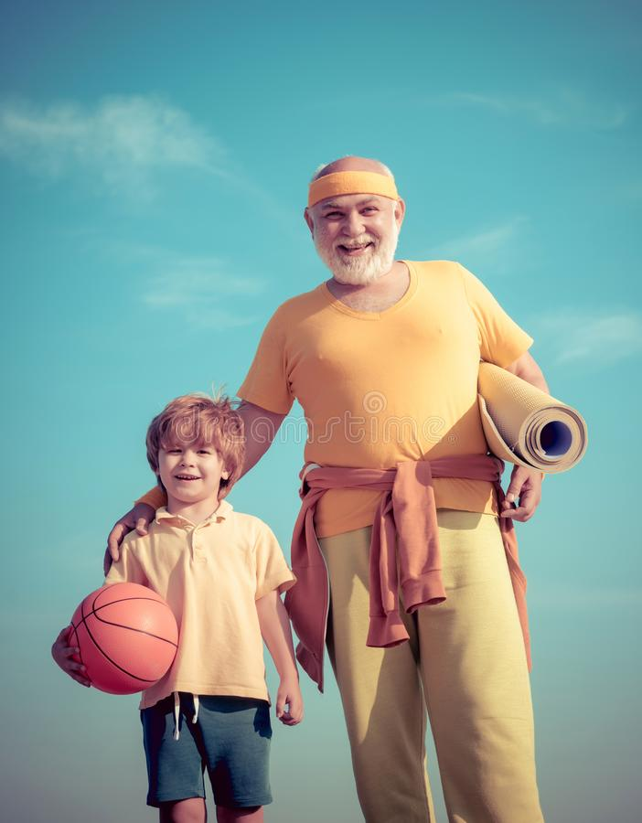 Father and son sporting - family time together. Doing sports is free. Family sport. Portrait of a healthy father and son. Working out over blue sky background stock photo