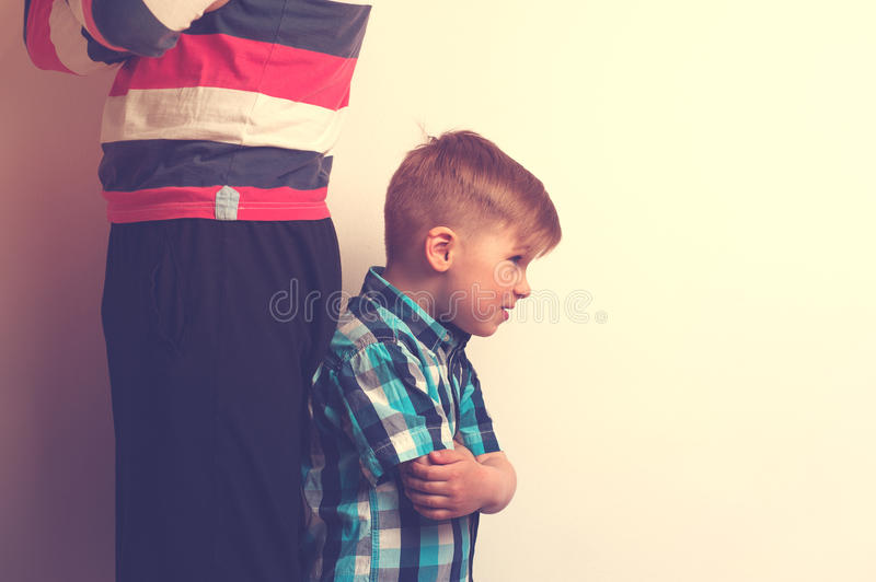 Father and son standing back to back after quarrel royalty free stock photo