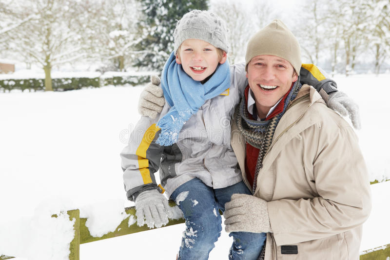 Father And Son Standing Outside In Snowy Landscape royalty free stock photo