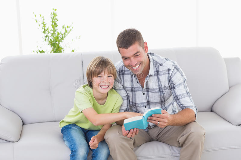 Father and son with story book sitting on sofa. Happy father and son with story book sitting on sofa at home royalty free stock photos