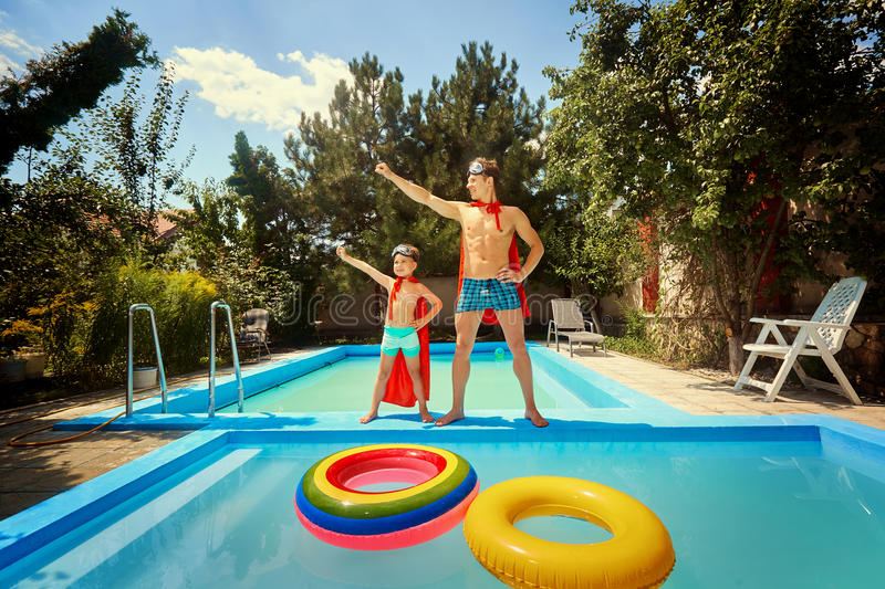 Father and son in suits of superheroes in the pool. stock image