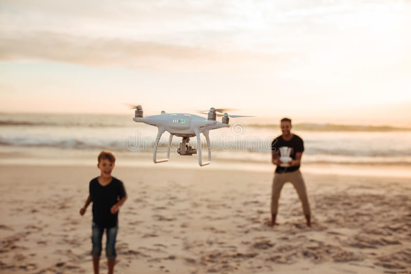 Father and son on summer vacation flying drone on beach stock photography