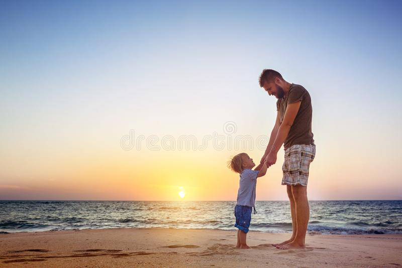 Father and son sunset beach tropics family vacations stock photo