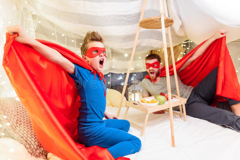 Father and son in superhero costumes having fun together in blanket fort royalty free stock image