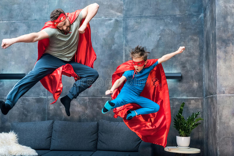 Father and son in superhero costumes jumping on sofa stock images