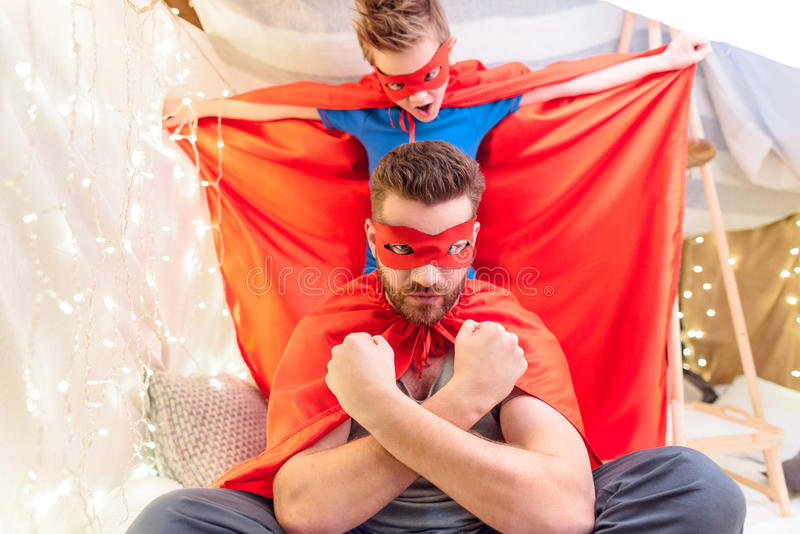 Father and son in superhero costumes playing together stock image