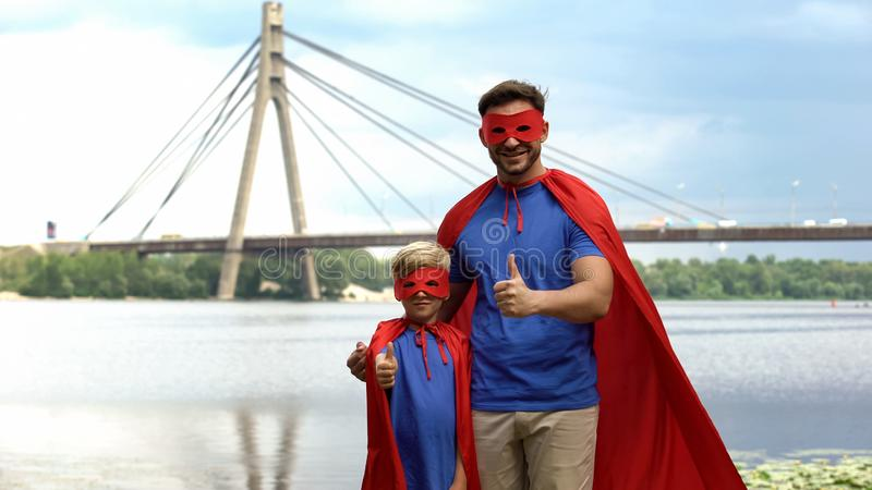 Father and son in superhero costumes showing thumbs up, motivation and teamwork royalty free stock photos