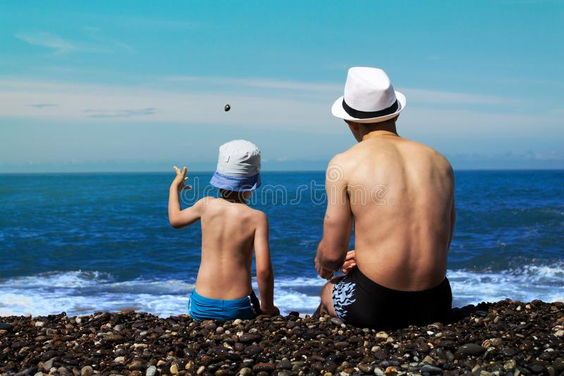 Father and son in swimming trunks are sitting by the surf. royalty free stock photo