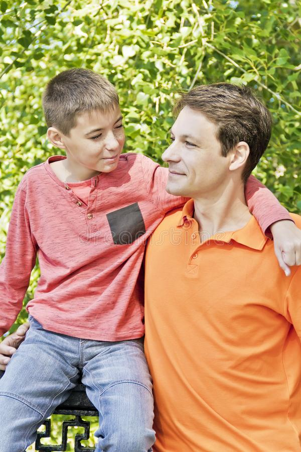 Father and teenager son together. Father and son are talking and looking to each others in summer royalty free stock images