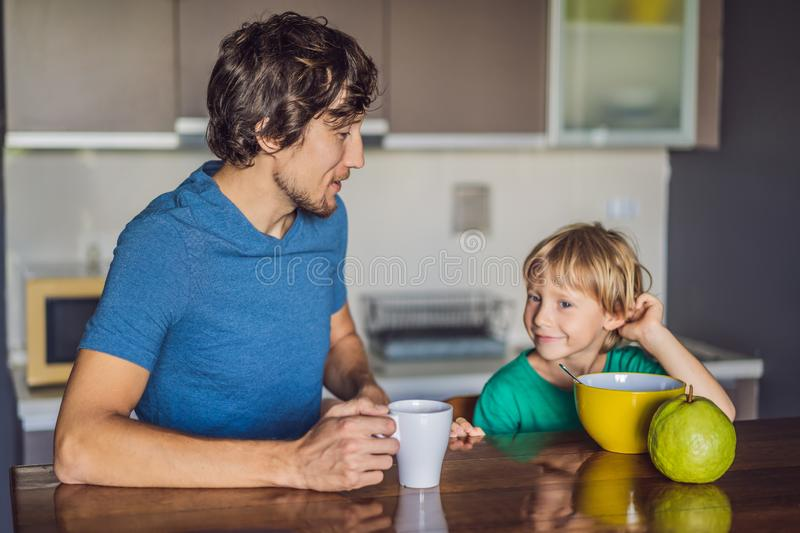 Father and son are talking and smiling while having a breakfast in kitchen stock photography