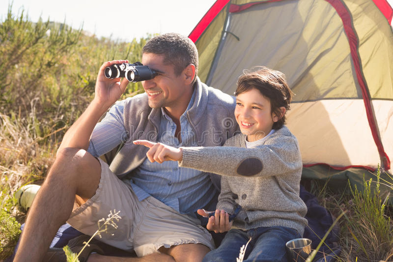 Father and son beside their tent in the countryside royalty free stock images