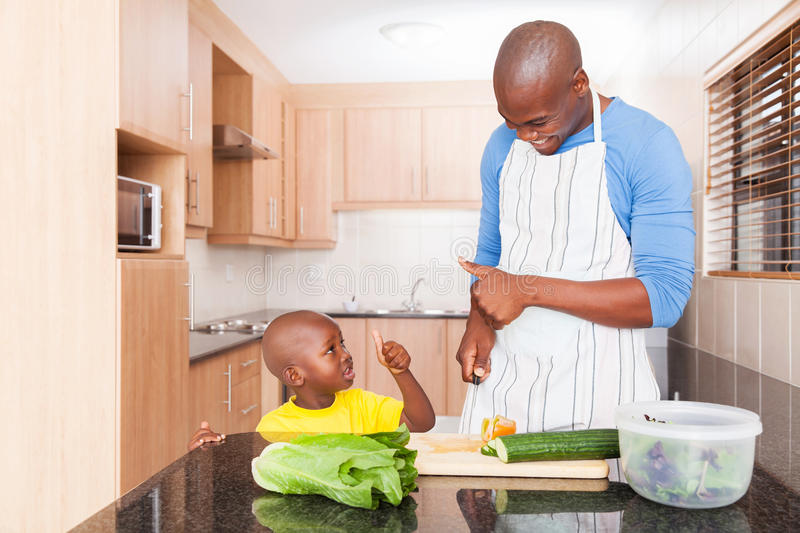 Father son thumbs up. Cheerful african father and son giving thumbs up in kitchen stock photo