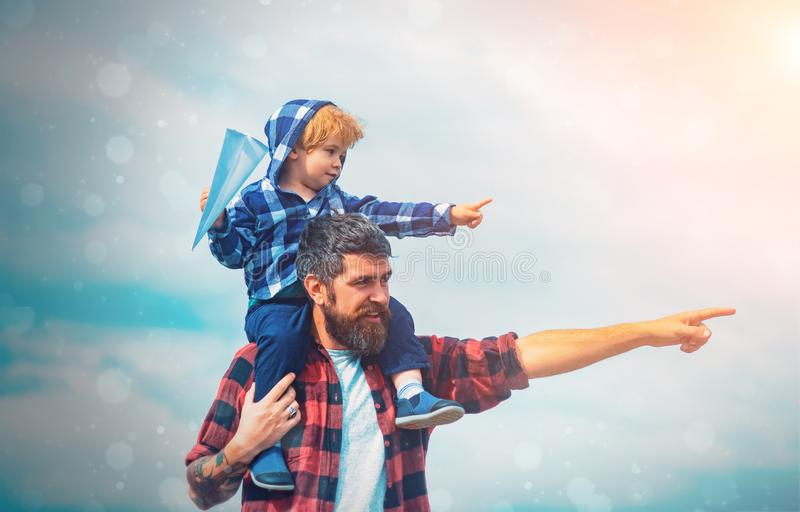Father and son together. Cute boy with dad playing outdoor. Childhood. Daddy and child son. Happy kid playing with paper royalty free stock image
