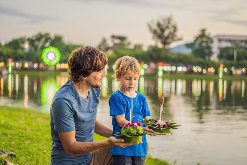 Father and son tourists holds the Loy Krathong in her hands and is about to launch it into the water. Loy Krathong. Festival, People buy flowers and candle to royalty free stock photos
