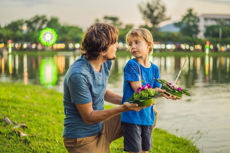 Father and son tourists holds the Loy Krathong in her hands and is about to launch it into the water. Loy Krathong. Festival, People buy flowers and candle to royalty free stock image