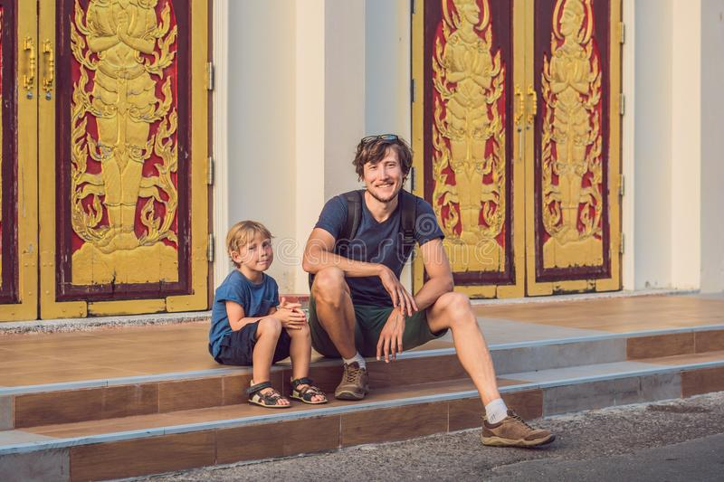 Father and son tourists in Thai temple in Phuket Town Wat Mongkolnimit stock image