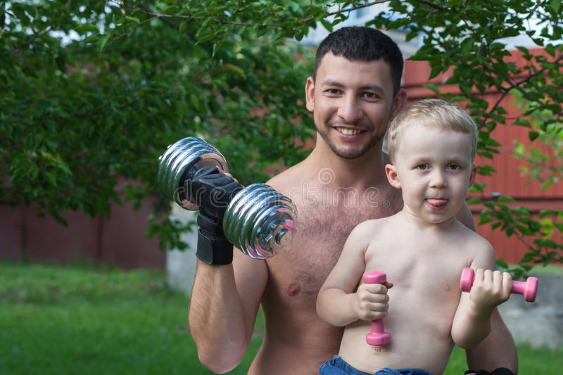 Father And Son Train With Dumbbells Royalty Free Stock Image