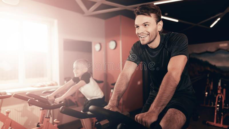 Father And Son Training On Bike Trail In The Gym. stock photos